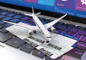 Boletos de avión en computadora y avión de juguete