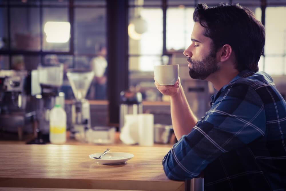 hombre degustando taza de café